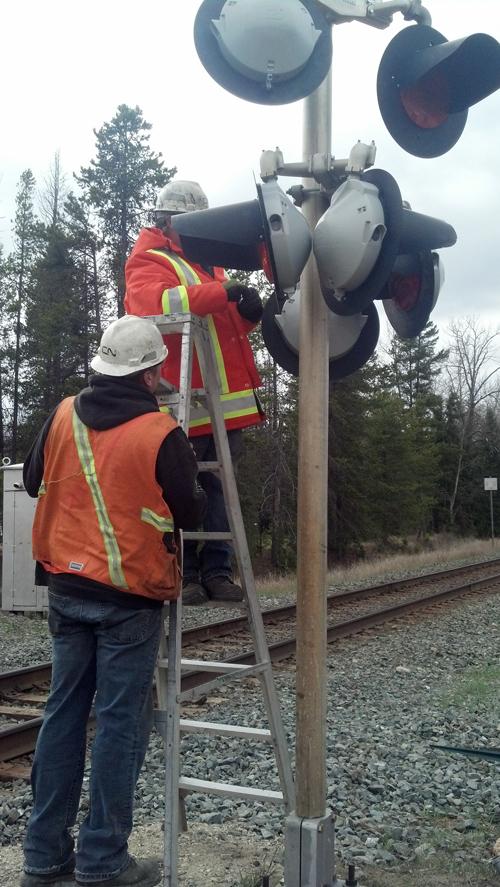Workers repair train signal light
