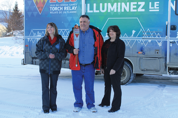 McBride Councillors  and Regional District rep hold the Winter Games torch on its tour through McBride.