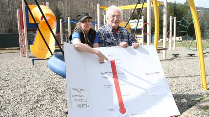 Chantal Swets and Pete Amyoony, two of the Dunster Fine Arts School Society members hold up their fundraising sign which now reaches the top. The Society has had to raise close to $1000 a month for the past six years in order to cover mortgage payments and operational expenses.