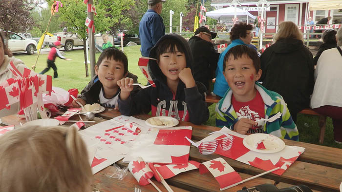 Noah and William Kim and Jayden Han took a moment from eating Canada Day cake to smile for the camera
