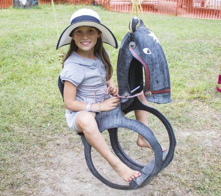 Photo: Maddi Pickerl Eliana Huzovicova rides the horse swing in the kid's area on Sunday.