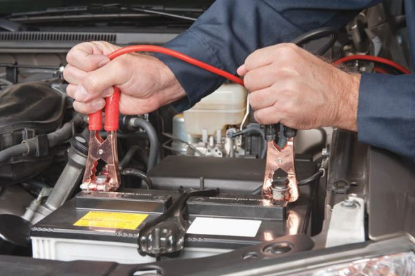 A car mechanic uses battery jumper cables to charge a dead battery.
