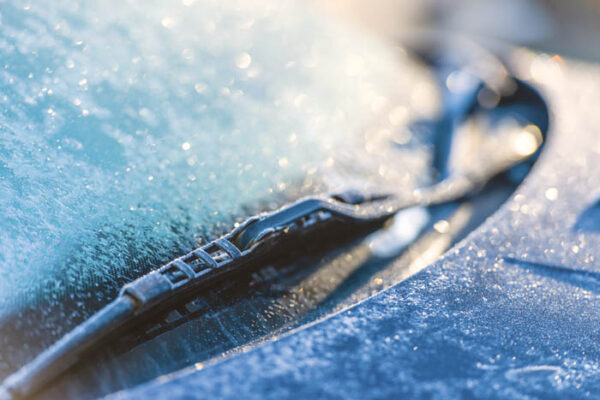 Frozen windshield, cold weather, sunlight on backlight, focus on foreground